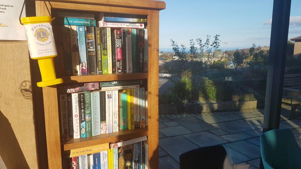 Wooden book shelf in Polmanter reception full of books