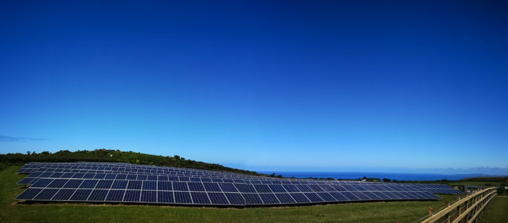 Field of solar panels, with the sea in the distance and bright blue skies