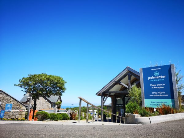 Polmanter sign in front of reception building with bright blue sky and the sea in the background