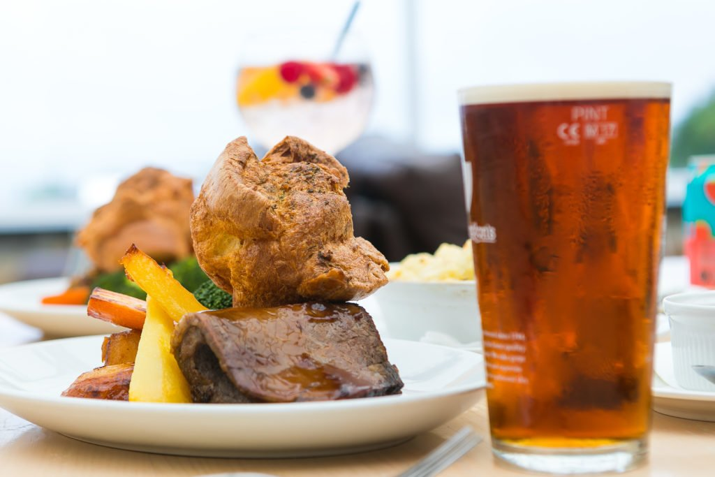 Roast beef dinner with Yorkshire pudding and a cold pint of beer