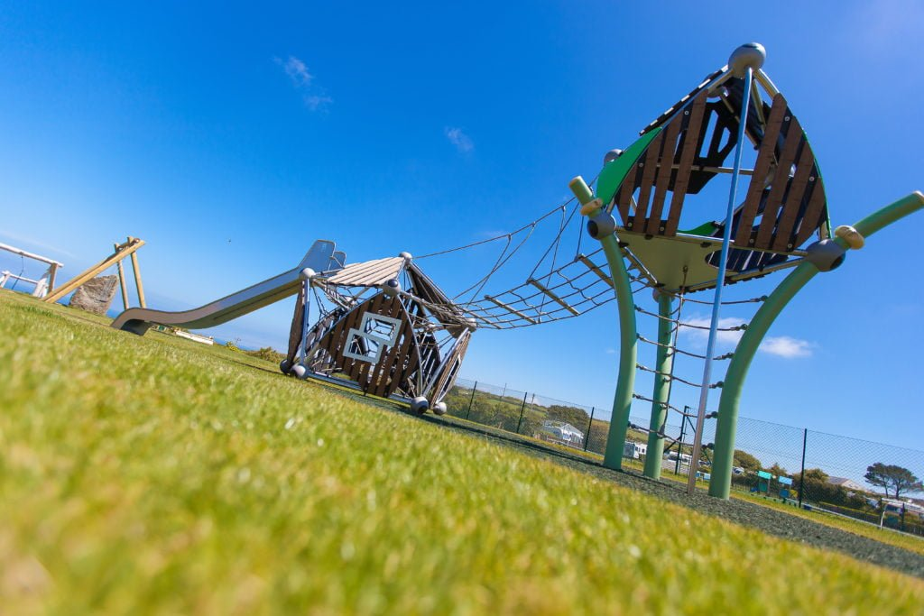 Climbing frame and slide with green grass and bright blue sky