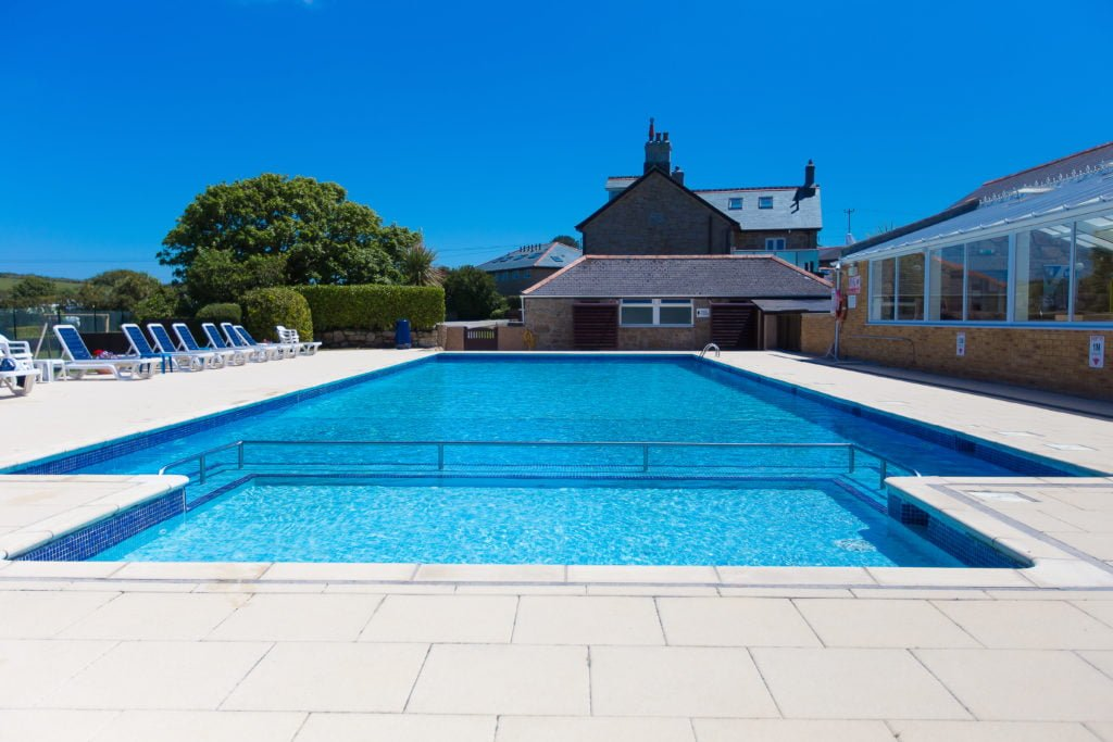 View of Polmanters swimming pool from the shallow end with sun loungers and bright blue sky