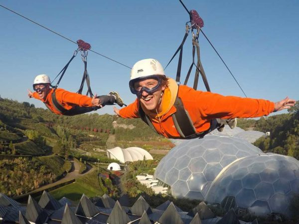 Two smiling people flying high above the Eden biomes on a zipwire