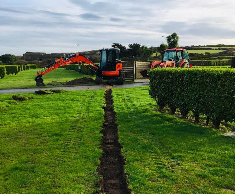 Digger digs trench through the grass